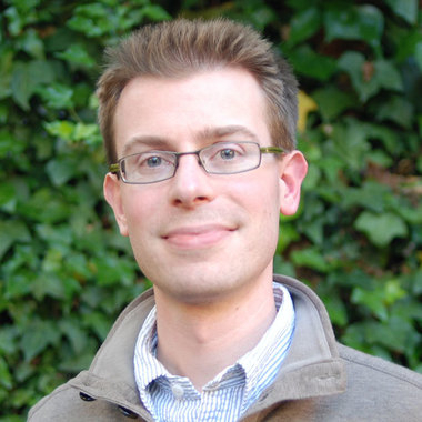 Headshot photo of Matt Brictson, Director of Engineering at Carbon Five in front of a green leafy background